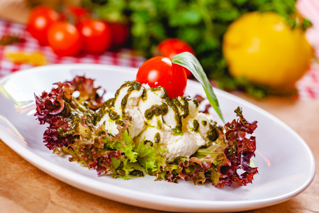 Italian burrata cheese served with cherry tomato, pesto sauce and lettuce leaves on white plate. Close up Zdjęcie Seryjne