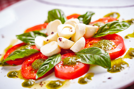 Traditional Italian caprese salad with sliced tomatoes, mozzarella cheese, basil and pesto sauce on white plate. Close up