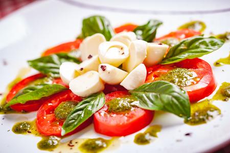 Traditionele Italiaanse caprese salade met gesneden tomaten, mozzarella kaas, basilicum en pestosaus op witte plaat. Detailopname Stockfoto