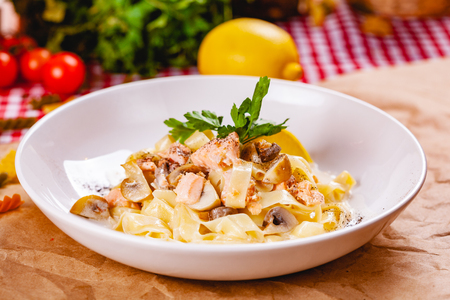 Pasta with salmon and mushrooms on white plate. Close up Zdjęcie Seryjne - 121183700