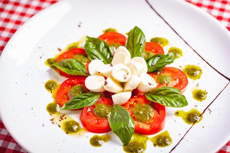 Traditional Italian caprese salad with sliced tomatoes, mozzarella cheese, basil and pesto sauce on white plate. Close up Zdjęcie Seryjne - 121183701