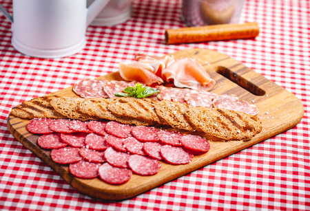 Italian meat and toasted bread on wooden cutting board. Close up Zdjęcie Seryjne - 121183702