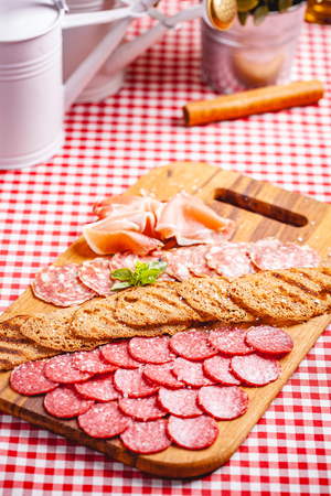 Italian meat and toasted bread on wooden cutting board. Close up
