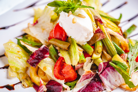 Salad with green beans, tomatoes, bell pepper, ricotta cheese and mixed greens on white plate. Close up Zdjęcie Seryjne