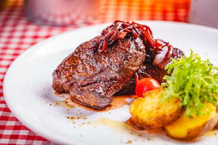 Steak de boeuf grillé servi avec pomme de terre sur plaque blanche. Fermer