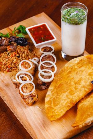 Middle eastern cuisine. Pasties, kebabs, pilaf, ayran on wooden cutting board. Close up Zdjęcie Seryjne - 121183733