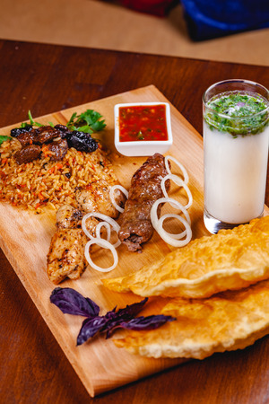 Middle eastern cuisine. Pasties, kebabs, pilaf, ayran on wooden cutting board. Close up Zdjęcie Seryjne - 121183742