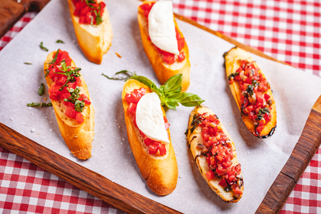 Traditional Italian bruschetta with cherry tomatoes, basil and mozzarella cheese on wooden cutting board. Close up