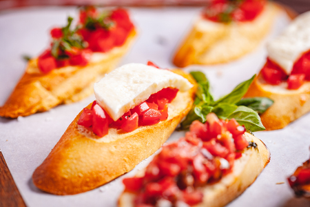 Traditional Italian bruschetta with cherry tomatoes, basil and mozzarella cheese on wooden cutting board. Close up Zdjęcie Seryjne - 121183744