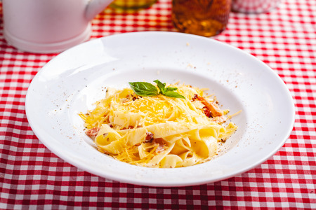 Italian cuisine. Pasta carbonara with bacon, cheese and egg on white plate. Close up Zdjęcie Seryjne - 121183745