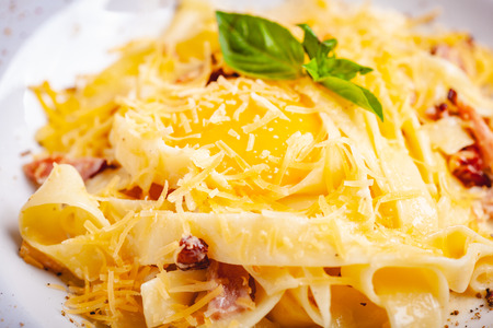 Italian cuisine. Pasta carbonara with bacon, cheese and egg on white plate. Close up Zdjęcie Seryjne - 121183746