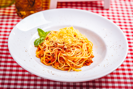 Italian cuisine. Spaghetti bolognese with meat, parmesan cheese and tomatoes on white plate. Close up Zdjęcie Seryjne