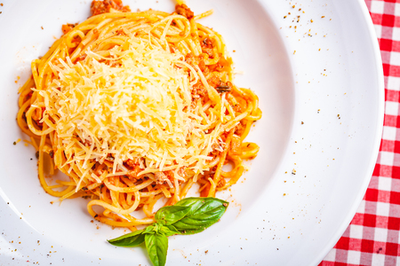 Italian cuisine. Spaghetti bolognese with meat, parmesan cheese and tomatoes on white plate. Top view. Close up Zdjęcie Seryjne