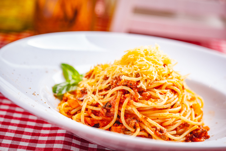 Italian cuisine. Spaghetti bolognese with meat, parmesan cheese and tomatoes on white plate. Close up Zdjęcie Seryjne - 121183750