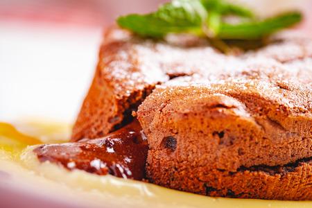 Chocolate fondant served with custard cream on white plate. Lava cake recipe. Close up