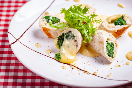 Steamed chicken cutlets stuffed with spinach on white plate. Close up Zdjęcie Seryjne - 121183783