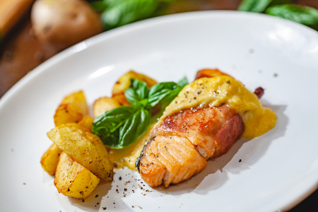 Grilled salmon fillet wrapped in bacon and potato wedges on white plate. Close up Zdjęcie Seryjne - 121183818