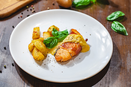 Grilled salmon fillet wrapped in bacon and potato wedges on white plate. Close up