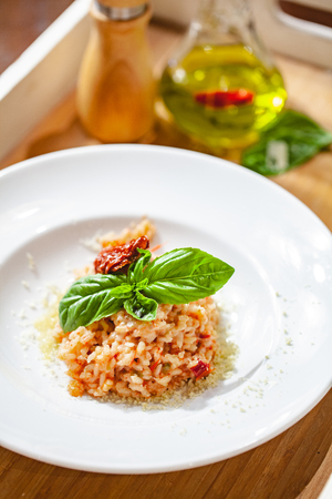 Risotto with sun-dried tomatoes and capers on white plate. Close up Zdjęcie Seryjne