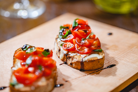 Traditional Italian bruschetta with cherry tomatoes, cheese, basil and balsamic vinegar on wooden board. Close up Zdjęcie Seryjne - 121183879