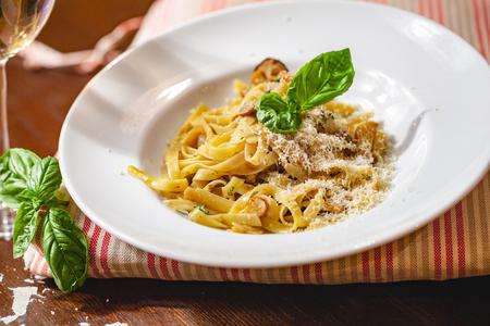 Italian pasta with mushrooms and parmesan cheese on white plate. Close up Zdjęcie Seryjne - 121183905