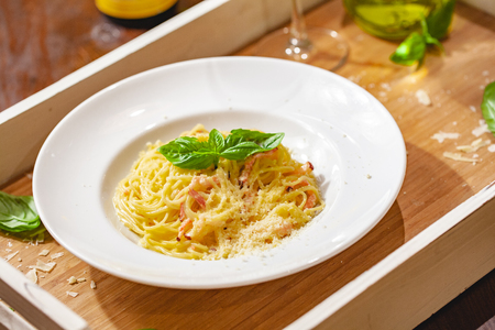 Italian spaghetti Carbonara with bacon and cheese on white plate. Close up