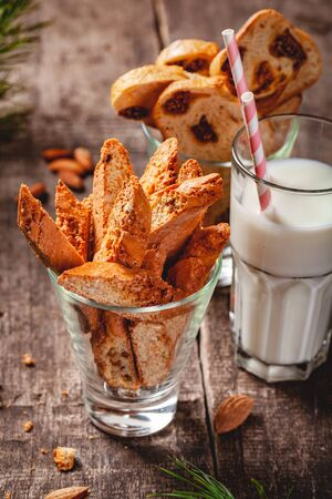 Biscotti or cantucci with milk on wooden rustic table. Close up. Christmas or New Year food concept