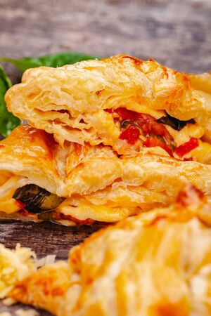 Puff pastry with cherry tomatoes, mozzarella cheese and basil on wooden rustic table. Close up Zdjęcie Seryjne