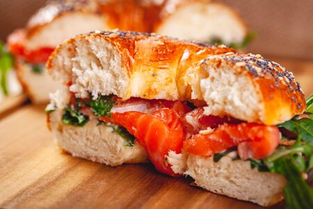 Bagel with cream cheese, smoked salmon and arugula salad cut in half on wooden board. Close up Zdjęcie Seryjne