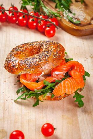 Bagel with cream cheese, smoked salmon and arugula salad on wooden board. Close up
