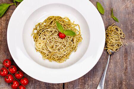 Italian pasta spaghetti with homemade pesto sauce on white plate. Top view. Close up Zdjęcie Seryjne