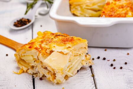 Potato gratin on wooden rustic table. Close up
