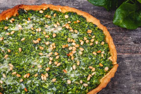 Tart with spinach, ricotta cheese and pine nuts on wooden rustic table. Close up