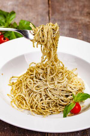 Italian pasta spaghetti with homemade pesto sauce on white plate. Close up Zdjęcie Seryjne