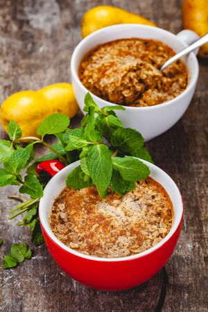 Apple crumble in two cups on wooden rustic background. Close up