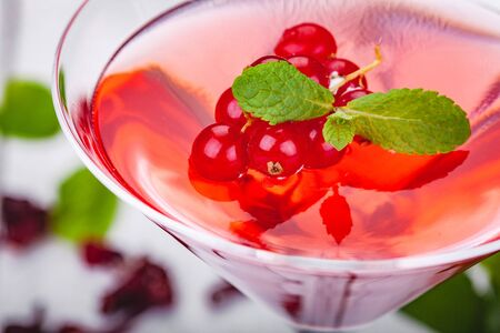 Jelly with red currant  in martini glass on wooden background. Close up