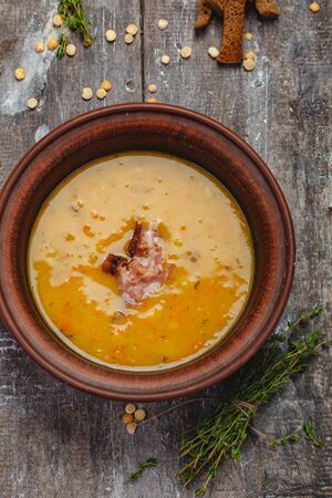 Pumpkin pea soup with bacon on wooden background. Top view. Close up