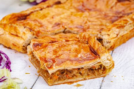 Homemade cabbage pie on wooden rustic background. Close up
