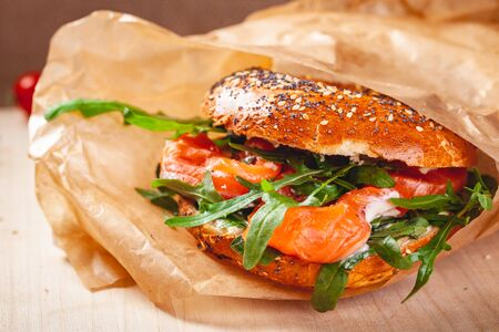 Bagel with cream cheese, smoked salmon and arugula salad in brown paper bag. Close up