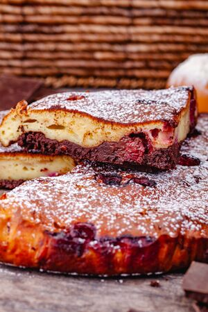 Brownie with cherries on wooden rustic table. Close up