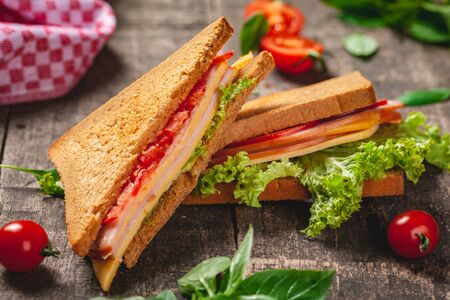 Sandwich with ham, cheese, tomatoes and lettuce leaves on wooden rustic table. Close up