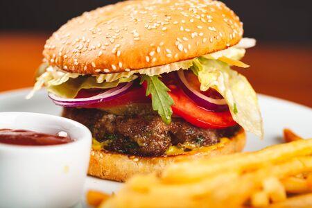Fast food. Hamburger maison et frites sur plaque blanche.