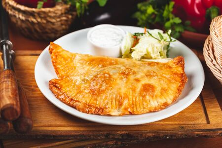 Traditional Crimean Tatar food chebureks with minced meat served with sour cream on white plate.