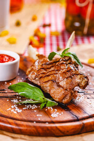 Rack of lamb fried with aromatic olive oil, herbs and spices on wooden board. Close up Archivio Fotografico
