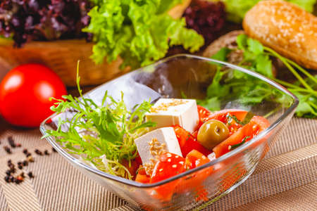 Salad with tomatoes, herbs and cheese in glass bowl Banque d'images