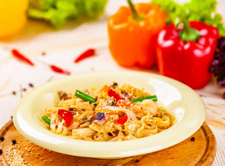 Pasta with seafood and vegetables in white plate on wooden cutting board