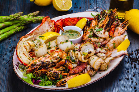 Seafood platter. Grilled lobster, shrimps, scallops, langoustines, octopus, squid on white plate.
