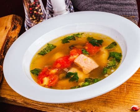 Fish soup with vegetables and salmon in white plate