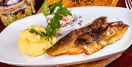 Fried fish and mashed potatoes on a white plate