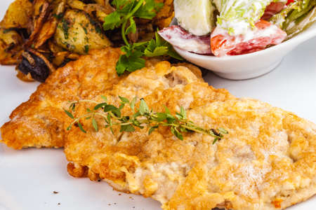 Chicken schnitzel with vegetable salad and fried potatoes with mushrooms on a white plate Standard-Bild